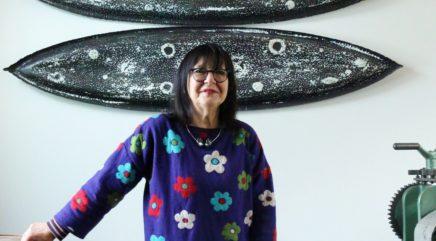 Kukkapaitainen nainen poseeraa taideteostensa edessä