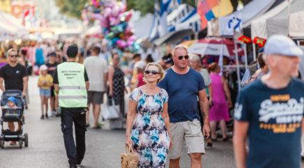 Ihmisiä kävelemässä markkinakojujen keskellä