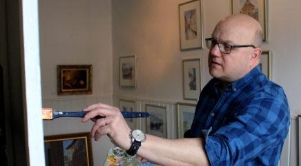Taiteilija maalaa teosta sinisessä paidassa