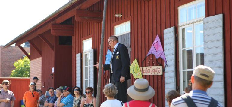 Mies puhumassa punaisen talon edessä ja yleisöä katsomassa