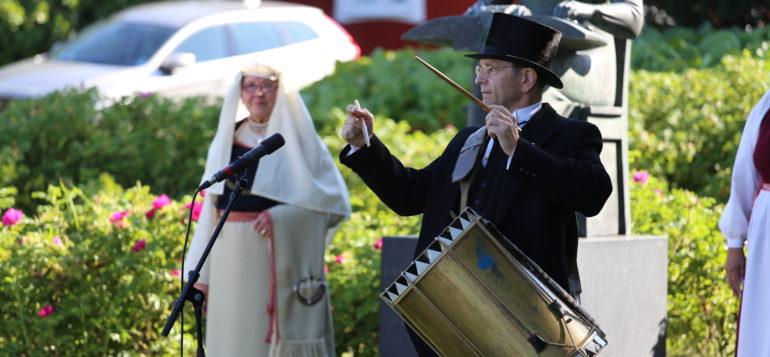 Mustaan pukuun pukeutunut mies rummuttaa rumpua, taustalla kansallispukuun pukeutuneita naisia