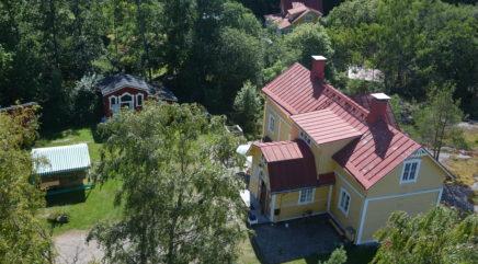 Ylhäältä päin kuvattuna keltainen talo ja sen pihapiiri