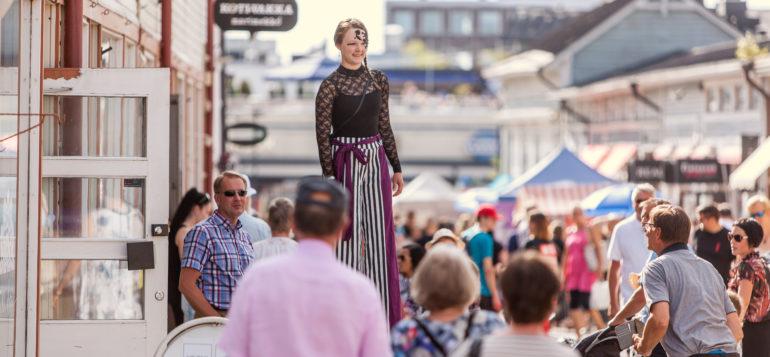 Mustaan pitsiin pukeutunut nainen kävelee puujaloilla ihmismassan joukossa kävelykadulla