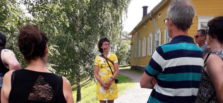 Nainen puhumassa opastuskierroksella ja ihmisiä kuuntelemassa