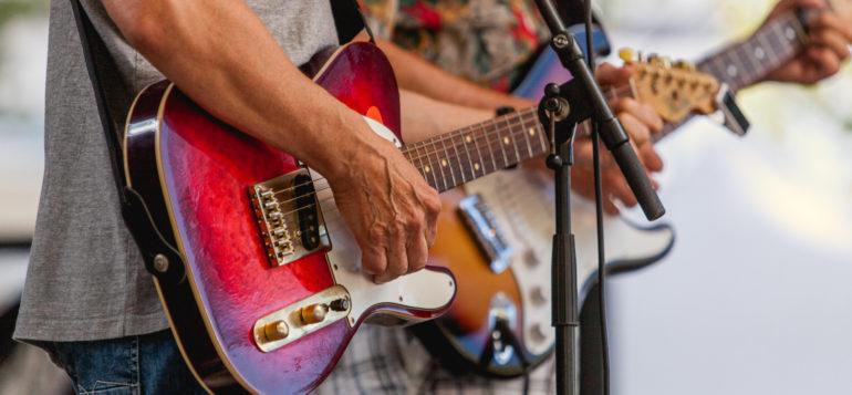 Miehet soittavat kitaraa