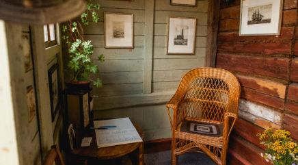 Sisäänkäynti näyttelyyn, valoisassa eteisessä nojatuoli ja vieraskirja