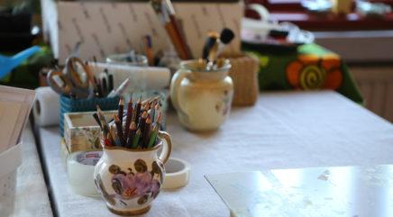 Vaalealla pöydällä taiteilijantarvikkeita, kuten kyniä, purkeissa
