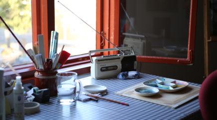 Ikkunan edessä olevalla pöydällä vanha radio sekä taiteilijatarvikkeita
