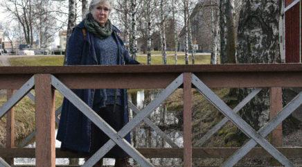Nainen seisoo sillalla, jonka kaiteet on tehty puusta
